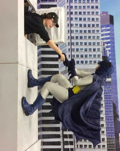 cosplayer pretends to be 1966 Batman climbing wall
